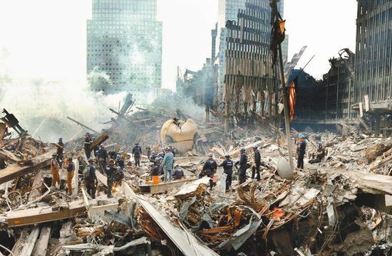 图为911事件发生时,世贸双子星大楼地面的断垣残骸景象 路透