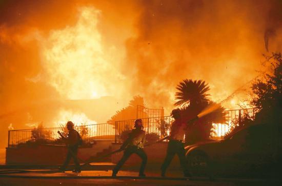 美国加州洛杉矶郡的野火十一日凌晨烧到民宅,消防员忙著扑灭火势。 (法新社)