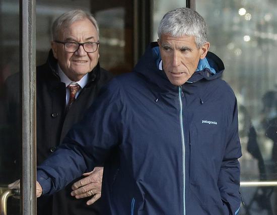 歷來最大規模的大學入學行賄舞弊案主嫌辛格(右)在波士頓法院過堂後,離開法院。 (美聯社)