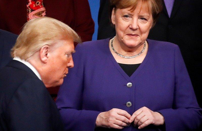 德美关系近来急速恶化,图为去年底北约峰会成员国领袖准备合照时,德国总理梅克尔看著川普从眼前走过画面。法新社