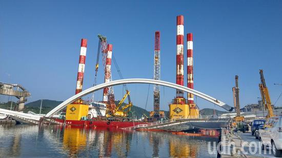 宜蘭南方澳跨港斷橋尚在拆除中,目前吊起一側的鋼拱(右),預計延後2小時開放臨時航道。 記者戴永華/攝影