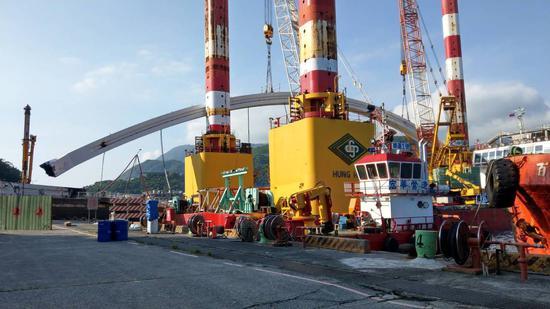 宜蘭南方澳跨港斷橋尚在拆除中,目前吊起一側的鋼拱,預計延後2小時開放臨時航道。 記者戴永華/攝影