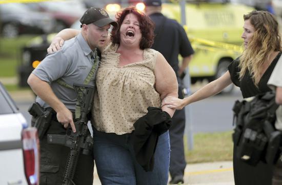 美国威斯康辛州软体公司「WTS Paradigm」19日发生枪击案,造成四人受伤,图中一名女性由警方搀扶离开现场时情绪激动。美联社