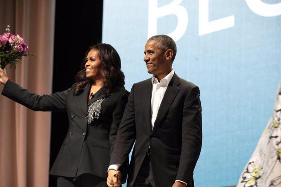 美国前总统奥巴马(图右)今天带著粉红玫瑰花束,现身米歇尔.奥巴马(图左)的打书会。 撷自米歇尔.奥巴马twitter