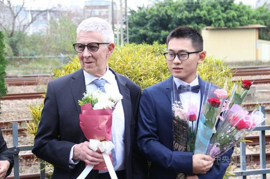 臺灣25歲青年趙守泉(右)與76歲英國老爹Andy(左)108年2月在苗栗家鄉舉辦婚禮,事隔約一年,兩人在苗栗市戶政事務所完成登記,成爲合法同婚伴侶。圖爲108年兩人公開接受衆人獻花祝福。中央社記者管瑞平攝 109年2月14日