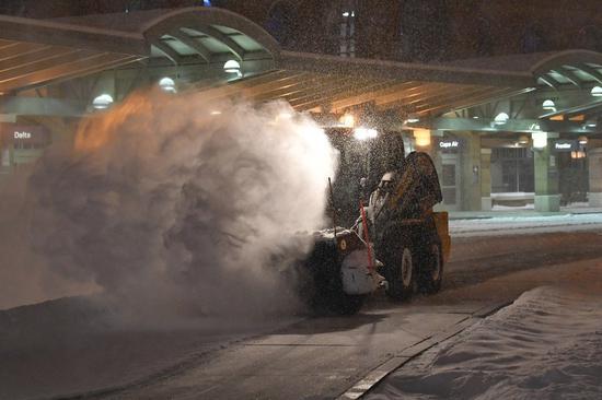 大雪纷茫,纽约州奥尔巴尼国际机场员工20日忙著铲雪。(美联社)