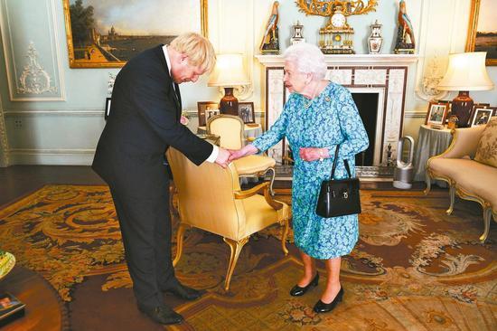英国首相强生(左)若拒绝延后脱欧,英国下议院可「恭请圣训」请求女王开除他 。图为强生上任时晋见女王。 美联社