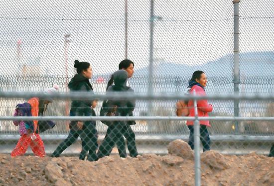 一些移民十日沿著美墨邊境步行前往美國邊境巡邏隊自首。 (法新社)