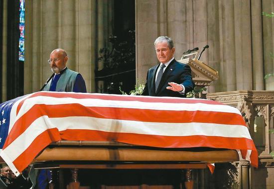 美國前總統小布什(右)五日在國葬儀式上輕撫父親老布什的靈柩。 (法新社)