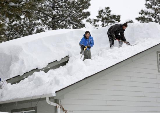 亚利桑纳州旗杆市降雪超过40吋,宣布进入紧急状态;居民们忙著清理屋顶的积雪,以免发生意外。(美联社)
