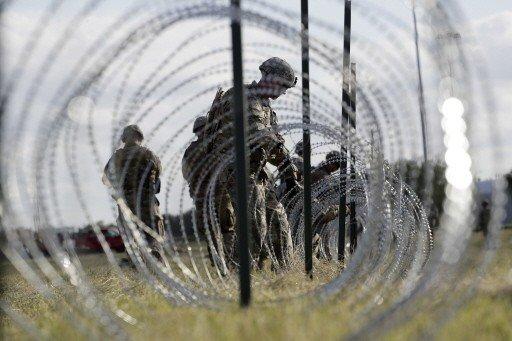 美国总统川普近来主打移民和边境安全议题,拉抬共和党在期中选举的选情。图为美国士兵在美墨边境附近放置蛇笼。 (美联社)