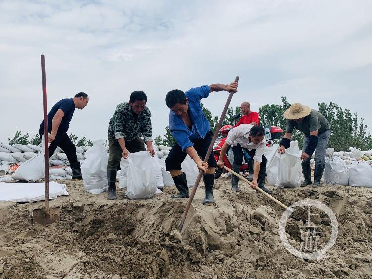 ▲7月13日,江西九江市江洲鎮,當地村民正在裝沙袋堤壩修築。攝影/上游新聞記者 時婷婷