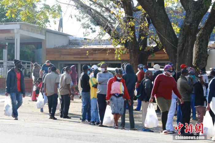 進入六月以來,南非新冠肺炎疫情呈現快速增長態勢。圖爲在南非約翰內斯堡一社會救濟站,領取救濟食品的民衆排成長龍。 中新社記者 王曦 攝