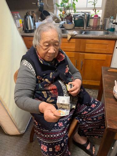 葉老太從錢夾掏出一百美金。(受訪者供圖)