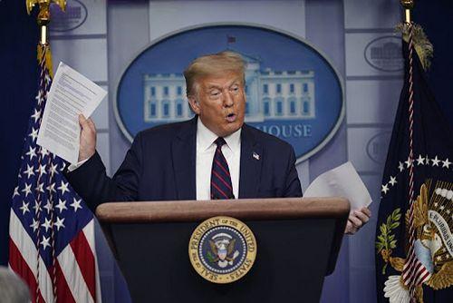 川普30日在疫情記者會上,拿著媒體報導表示,他並不想延後選舉。