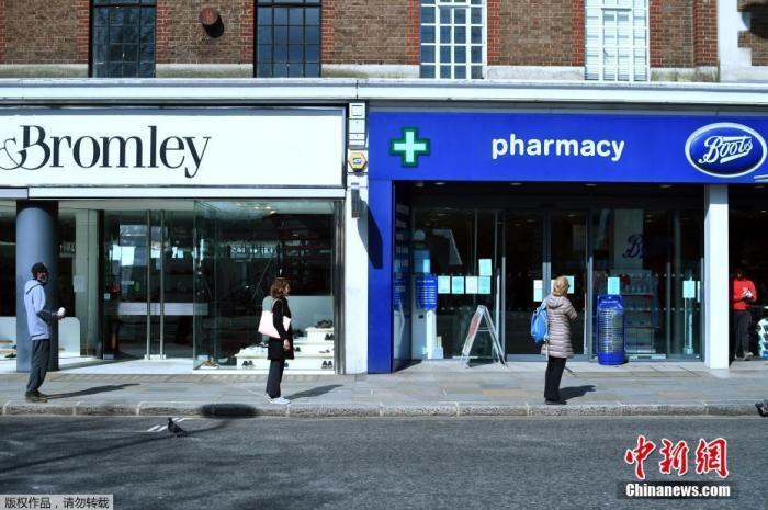 當地時間3月24日,英國倫敦,民衆保持着較遠的間隔在藥房外排隊。